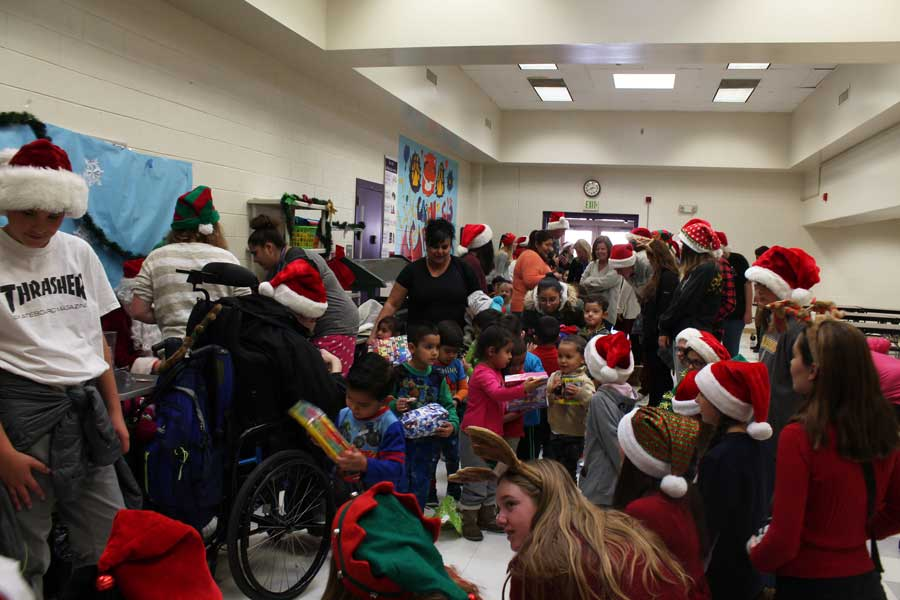 Kids at the Garden Place Academy pour into the cafeteria to receive their gifts.