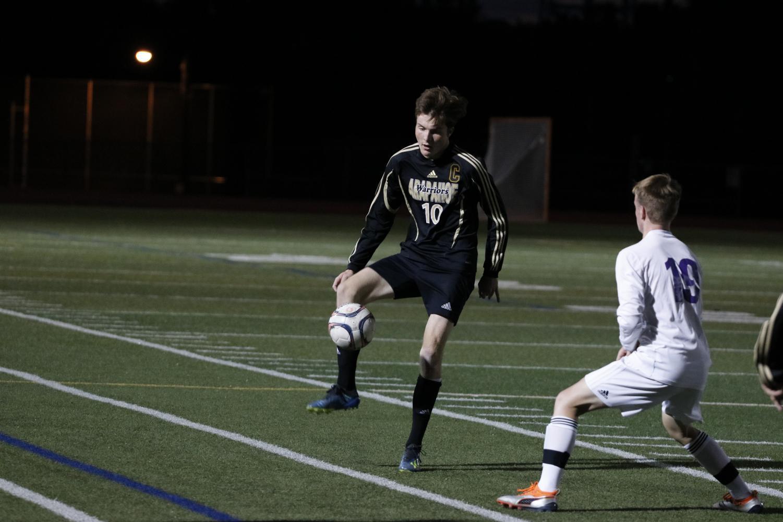 Senior Captain Connor Crookham handling ball against Littleton High School.