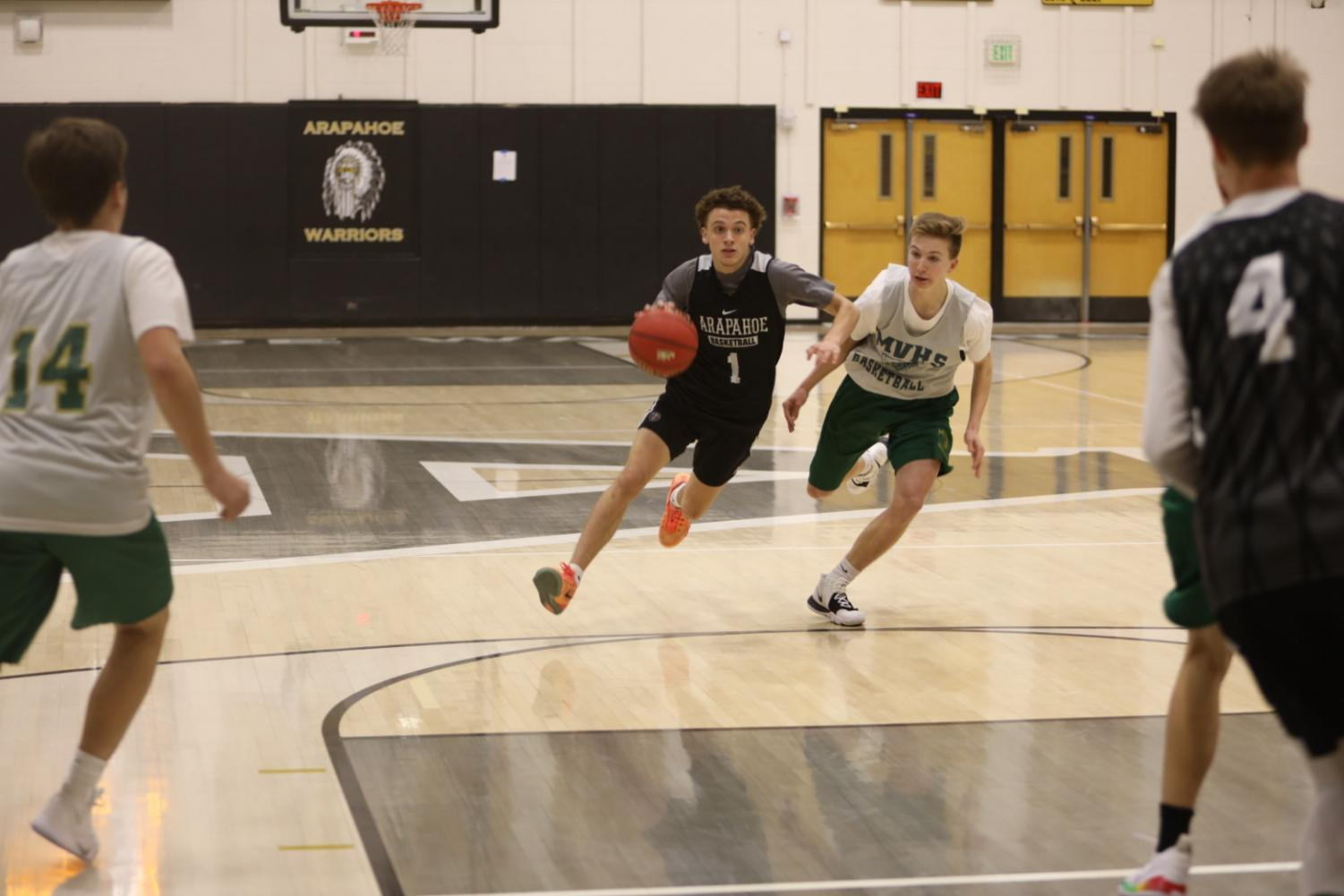 Korey Hess drives by Mountain Vista defender Nathan Miller in a friendly scrimmage on Saturday November 30, 2019.